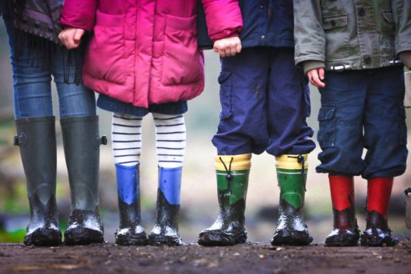 Vier Kinder mit Gummistiefeln stehen nebeneinander. Die Kinder sieht man ab dem Bauch bis zu den Füssen.